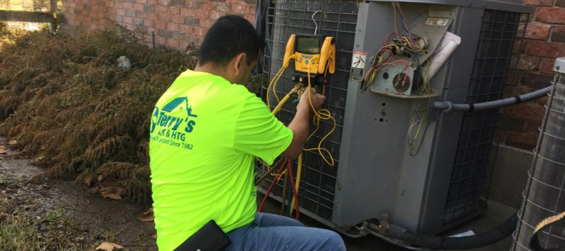 terrys-hvac-technician-assessing-an-outdoor-condenser