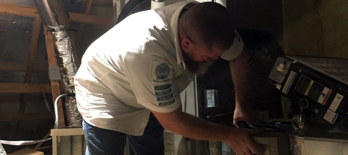 Rob Terry of Terry's A/C and Heating inspecting a furnace