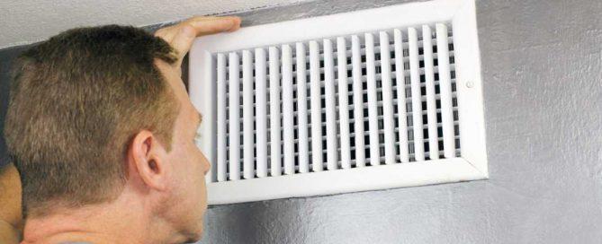 hvac technician looking at an air vent