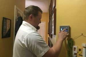 kenny inspects a smart thermostat