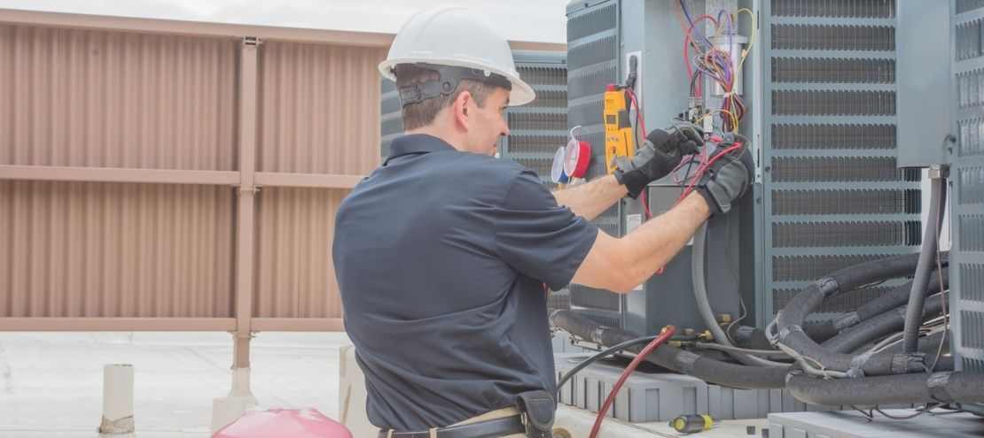AC service technician charges air conditioner with refrigerant